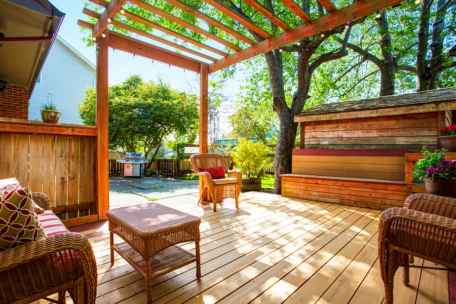 Backyard Deck With Wicker Furniture And Pergola